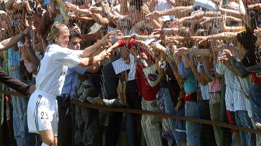 FILE - In this July 21, 2003, file photo, English soccer player David Beckham greets fans after his presentation by Real Madrid in Madrid, Spain. The 38-year-old midfielder, who recently won a league title in a fourth country with Paris Saint-Germain, said Thursday, May 16, 2013, he will retire after the season. (AP Photo/Paul White, File)