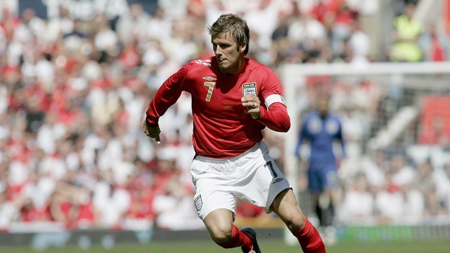 FILE- In this June 3, 2006, file photo, England's David Beckham dribbles the ball against Jamaica during their international friendly soccer match at Old Trafford Stadium, Manchester, England. The 38-year-old midfielder, who recently won a league title in a fourth country with Paris Saint-Germain, said Thursday, May 16, 2013, he will retire after the season.  (AP Photo/Dave Thompson, File)