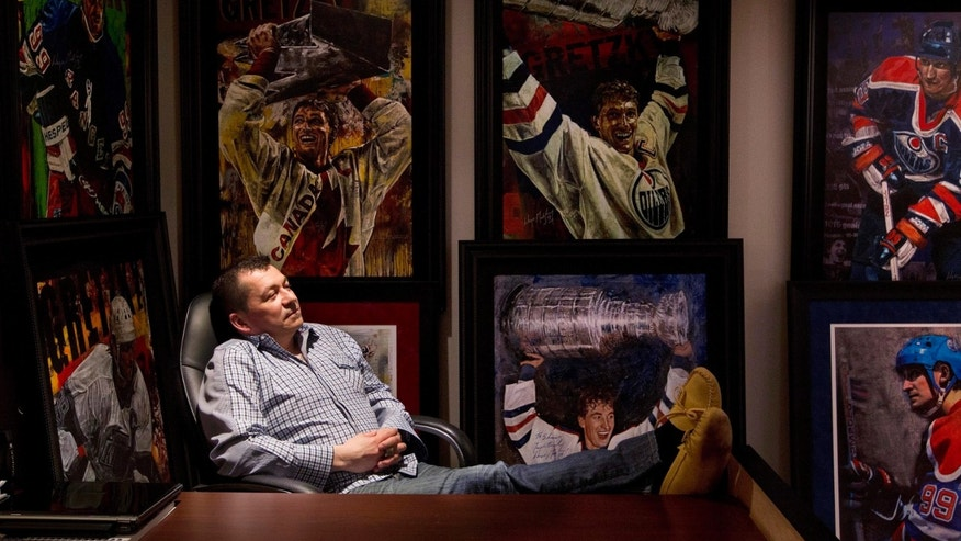 In this April 16, 2013 photo, Shawn Chaulk poses with his collection of Wayne Gretzky memorabilia in Fort McMurray, Alberta. Chaulk's hoard of everything Wayne Gretzky goes on the auction block Friday.  (AP Photo/The Canadian Press, Jason Franson)