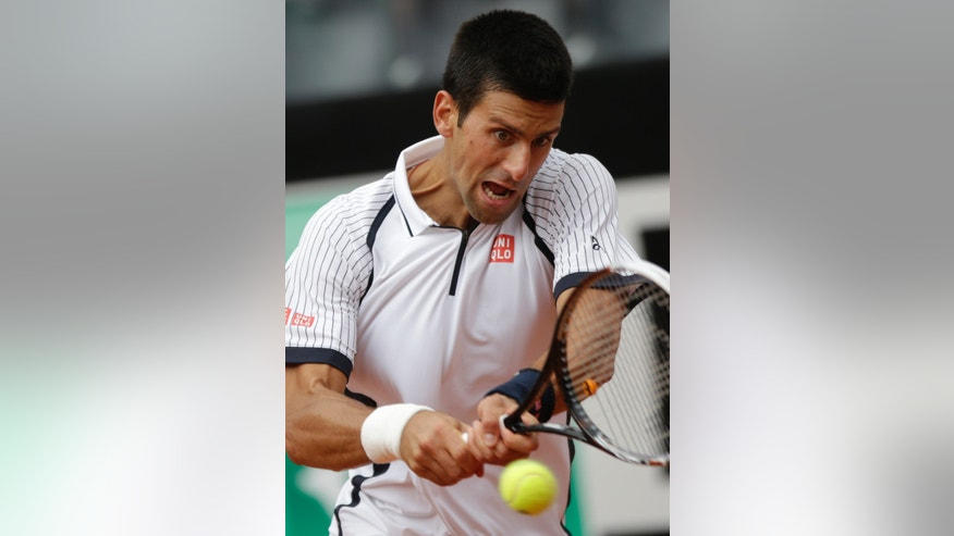 Serbia's Novak Djokovic returns the ball to Ukraine's Alexandr Dolgopolov during their match at the Italian Open tennis tournament in Rome, Thursday, May 16, 2013. Djokovic beat Dolgopolov 6-1, 6-4 and advanced to the quarterfinals. (AP Photo/Andrew Medichini)