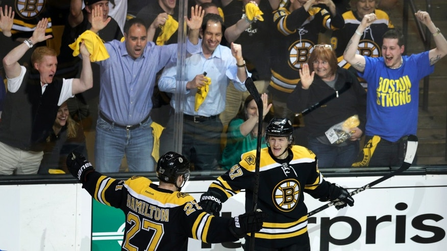 Fans, top, celebrate as Boston Bruins defenseman Torey Krug, front right, is congratulated by teammate Dougie Hamilton after his goal against the New York Rangers during the third period in Game 1 of an NHL hockey playoffs Eastern Conference semifinal game in Boston, Thursday, May 16, 2013. (AP Photo/Charles Krupa)