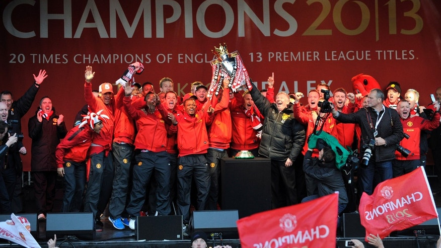 Manchester United's Alex Ferguson, centre right, lifts the Premier League trophy with Patrice Evra, centre left, during their premiership trophy parade, after winning the English Premier League, in Manchester, England, Monday May 13, 2013. Manager Alex Ferguson has retired after more than 26 years in charge at the club.  (AP Photo/Clint Hughes)