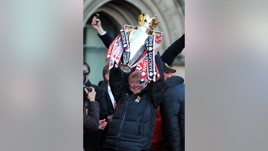 Manchester United's Alex Ferguson lifts the Premier League trophy during their premiership trophy parade, at Albert Square in Manchester, England, Monday May 13, 2013. Manager Alex Ferguson has retired after more than 26 years in charge at the club. (AP Photo/Clint Hughes)