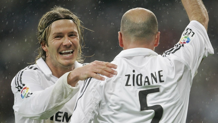 "FILE - This is a Sunday, Jan. 15, 2006 file photo of Real Madrid's David Beckham, left, as he congratulates  goalscorer Zinedine Zidane  during their Spanish league soccer match against Sevilla  at the Santiago Bernabeu Stadium in Madrid, Spain.  David Beckham is retiring from soccer after the season, ending a career in which he become a global superstar since starting his career at Manchester United. The 38-year-old Englishman recently won a league title in a fourth country with Paris Saint-Germain. He said in a statement Thursday May 16, 2013  he is ""thankful to PSG for giving me the opportunity to continue but I feel now is the right time to finish my career, playing at the highest level."" (AP Photo/Bernat Armangue, File)"