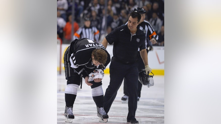 Los Angeles Kings center Anze Kopitar, of Slovenia,, left, is helped off the ice after getting hit in the face with a puck against the San Jose Sharks during the third period in Game 2 of their second-round NHL hockey Stanley Cup playoff series, Thursday, May 16, 2013, in Los Angeles.  (AP Photo/Mark J. Terrill)