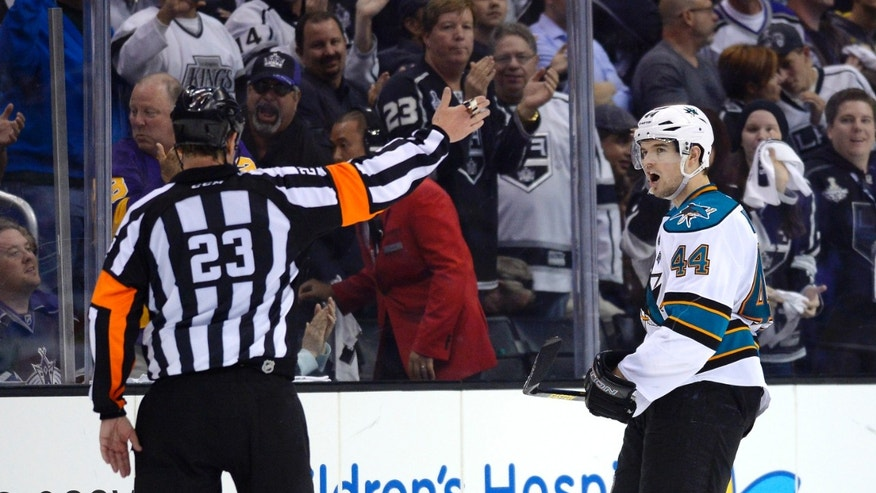 San Jose Sharks defenseman Marc-Edouard Vlasic, right, complains to referee Brad Watson after being called for a delay of game penalty during the third period in Game 2 of their second-round NHL hockey Stanley Cup playoff series against the Los Angeles Kings, Thursday, May 16, 2013, in Los Angeles.  (AP Photo/Mark J. Terrill)