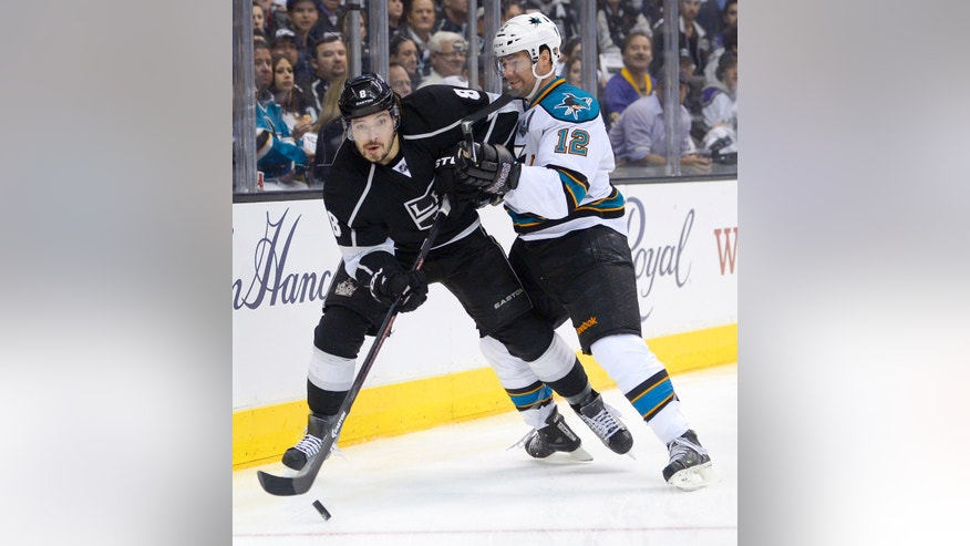Los Angeles Kings defenseman Drew Doughty, left, sends the puck away from San Jose Sharks center Patrick Marleau during the first period in Game 2 of a second-round NHL hockey Stanley Cup playoff series, Thursday, May 16, 2013, in Los Angeles.  (AP Photo/Mark J. Terrill)