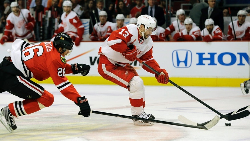 Detroit Red Wings' Pavel Datsyuk (13) controls the puck past Chicago Blackhawks ' Michal Handzus (26) during the first period of Game 1 of an NHL hockey playoffs Western Conference semifinal in Chicago, Wednesday, May 15, 2013. (AP Photo/Nam Y. Huh)