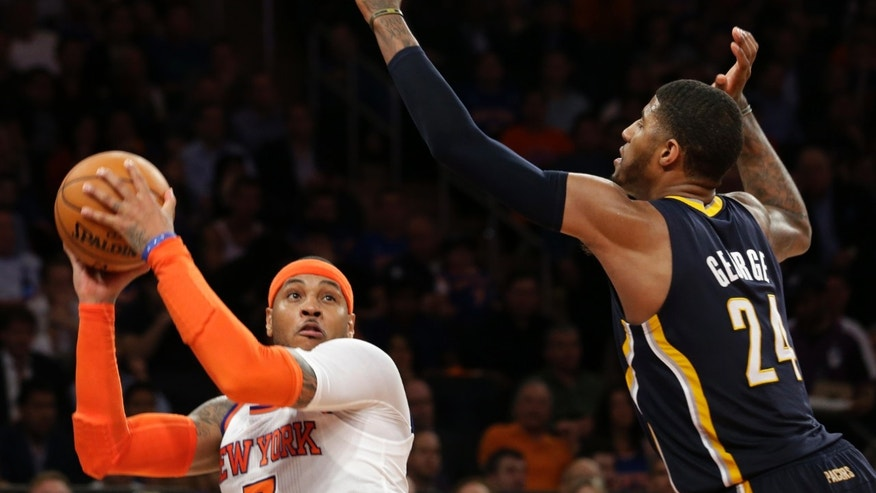 New York Knicks' Carmelo Anthony, left, goes up for a shot against Indiana Pacers' Paul George in the second half of Game 5 of an Eastern Conference semifinal in the NBA basketball playoffs, at Madison Square Garden in New York, Thursday, May 16, 2013. The Knicks won 85-75. (AP Photo/Julio Cortez)