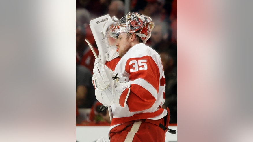 Detroit Red Wings goalie Jimmy Howard adjusts his facemask during the first period of Game 2 of the NHL hockey Stanley Cup playoffs Western Conference semifinals against the Chicago Blackhawks Saturday, May 18, 2013, in Chicago. (AP Photo/Nam Y. Huh)