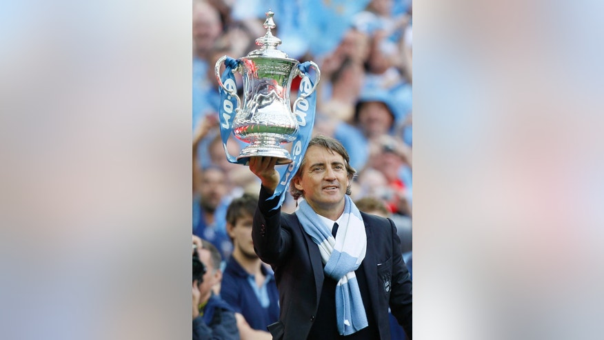 FILE - A Saturday, May 14, 2011 photo from files showing Manchester City's manager Roberto Mancini holding aloft the English FA Cup Trophy as he celebrates their win over Stoke City at Wembley Stadium, London. Manchester City has fired manager Roberto Mancini after conceding the Premier League title to rival Man United and finishing the season without a trophy. The club announced the decision Monday, May 13, 2013 on its website. The Italian is departing after less than four years in charge, having ended the club's 35-year trophy drought by winning the FA Cup in 2011 and then leading the team to its first league title in 44 years the following season. (AP Photo/Kirsty Wigglesworth, File)