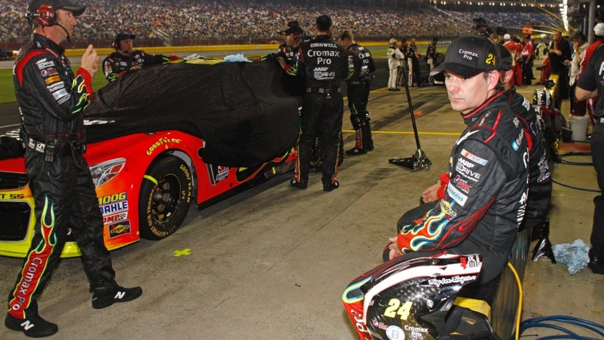 Jeff Gordon, right, sits on the pit-road wall as crew members cover his car during a rain delay in the NASCAR All-Star auto race at Charlotte Motor Speedway in Concord, N.C., Saturday, May 18, 2013. (AP Photo/Nell Redmond)