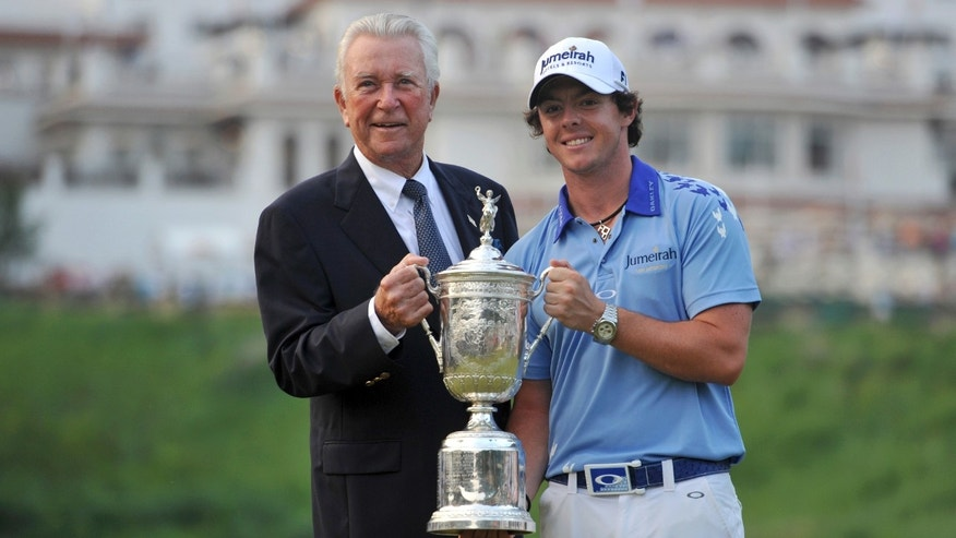 FILE - In this June 19, 2011, file photo, 2011 U.S. Open golf tournament champion Rory McIlroy holds his trophy with former winner Ken Venturi in Bethesda, Md. Venturi, who overcame dehydration to win the 1964 U.S. Open and spent 35 years in the booth for CBS Sports, died Friday afternoon, May 17, 2013. He was 82. His son, Matt Venturi, said he died in a hospital in Rancho Mirage, Calif. (AP Photo/Larry French, File)