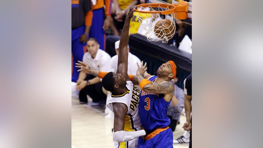 Indiana Pacers center Roy Hibbert, left, dunks over New York Knicks guard James White during the third quarter of Game 6 of the Eastern Conference semifinal NBA basketball playoff series in Indianapolis, Saturday, May 18, 2013. (AP Photo/Michael Conroy)
