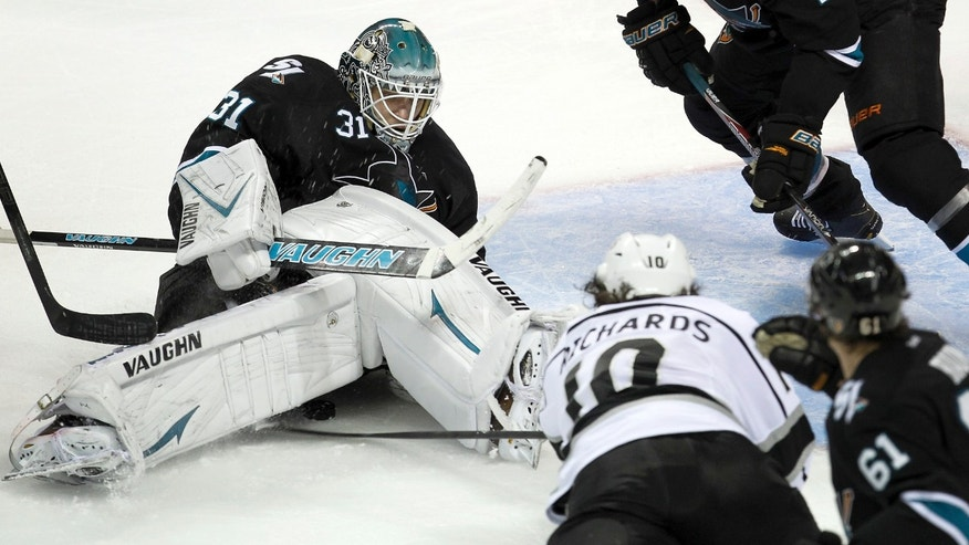 San Jose Sharks goalie Antti Niemi (31), of Finland, blocks a goal attempt against Los Angeles Kings center Mike Richards (10) as San Jose Sharks defenseman Justin Braun (61) looks on during the second period in Game 3 of their second-round NHL hockey Stanley Cup playoff series, Saturday, May 18, 2013, in San Jose, Calif. (AP Photo/Tony Avelar)