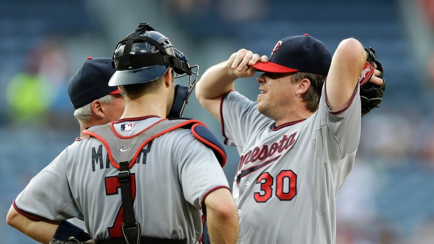 Minnesota Twins starting pitcher Kevin Correia (30) adjusts his cap as he talks with catcher Joe Mauer (7) and  pitching coach Rick Anderson (40) in the first inning of a baseball game against the Atlanta Braves Monday, May 20, 2013, in Atlanta. (AP Photo/John Bazemore)