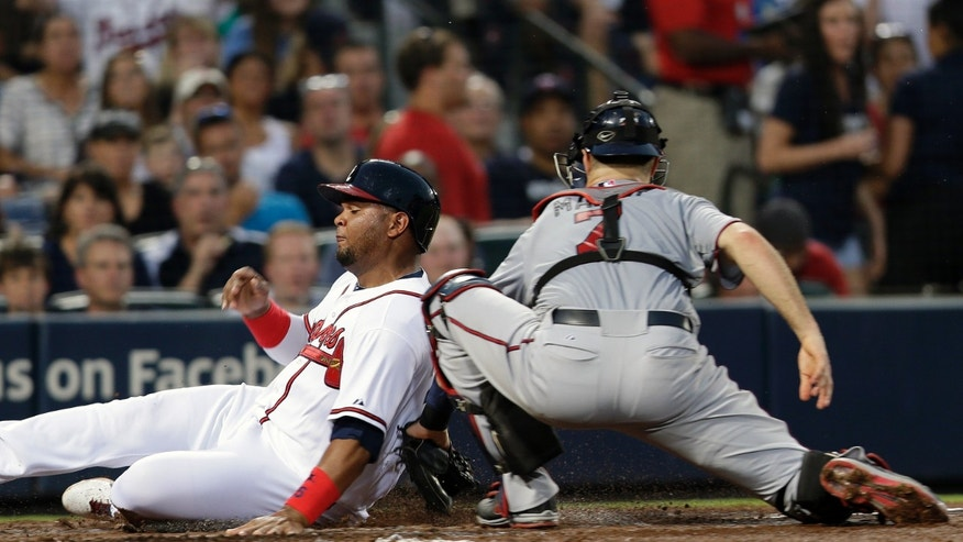 Atlanta Braves third baseman Juan Francisco (25) scores on an Anthrelton Simmons fly ball as Minnesota Twins catcher Joe Mauer (7) applies the late tag in the fourth inning of a baseball game Monday, May 20, 2013, in Atlanta. (AP Photo/John Bazemore)
