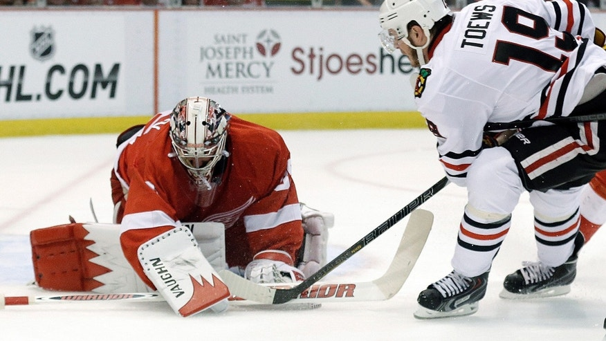 Detroit Red Wings goalie Jimmy Howard (35) stops a shot by Chicago Blackhawks center Jonathan Toews (19) during the first period of an NHL hockey Stanley Cup playoffs Western Conference semifinal game in Detroit, Monday, May 20, 2013. (AP Photo/Paul Sancya)