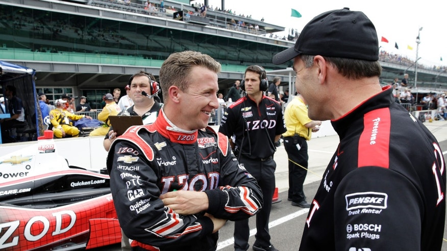 AJ Allmendinger, left, smile as he talks with a member of his crew after he qualified on the first day of qualifications for the Indianapolis 500 auto race at the Indianapolis Motor Speedway in Indianapolis, Saturday, May 18, 2013. (AP Photo/Tom Strattman)