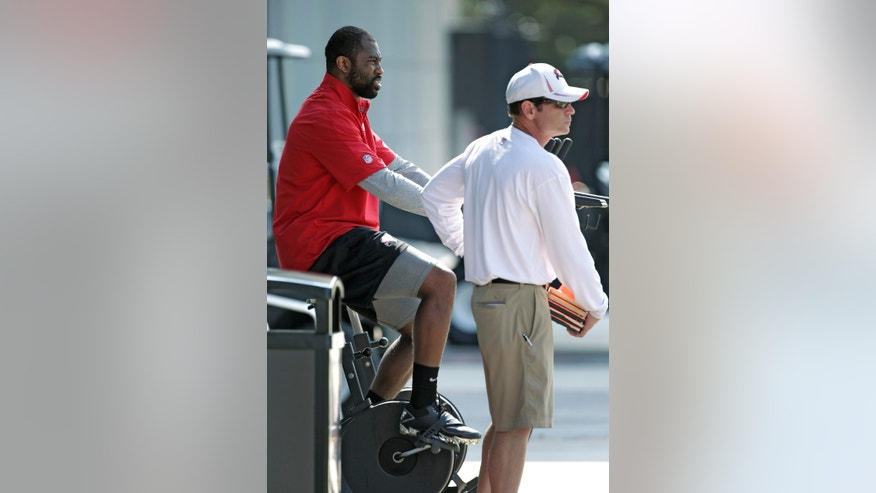 New Tampa Bay Buccaneers cornerback Darrelle Revis, left, rides a stationary bike as he talks to Todd Toriscelli, Director of Sports Medicine and Performance during an NFL football optional workout Monday, May 20, 2013, in Tampa, Fla. (AP Photo/Chris O'Meara)