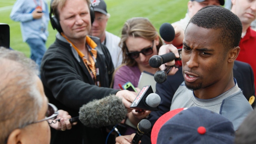 Denver Broncos free safety Rahim Moore, right, is surrounded by reporters after taking part in an off-season training camp at the NFL football team's training headquarters in Englewood, Colo., on Monday, May 20, 2013. (AP Photo/David Zalubowski)