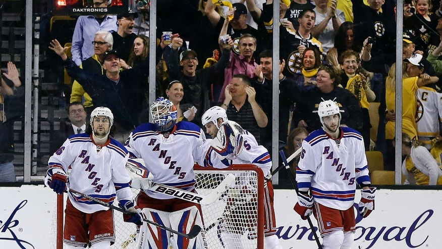 As fans, background, react, New York Rangers goalie Henrik Lundqvist, second from left, and teammates right wing Mats Zuccarello (36), defenseman Dan Girardi (5) and center Derick Brassard (16) react after the Boston Bruins scored their fifth goal during the third period in Game 2 of the NHL Eastern Conference semifinal hockey playoff series in Boston, Sunday, May 19, 2013. The Bruins won 5-2. (AP Photo/Elise Amendola)