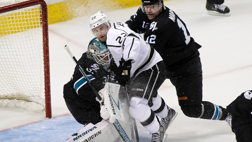 Los Angeles Kings center Trevor Lewis (22) collides with San Jose Sharks goalie Antti Niemi (31), of Finland, as San Jose Sharks center Patrick Marleau (12) defends during third period in Game 3 of their second-round NHL hockey Stanley Cup playoff series, Saturday, May 18, 2013, in San Jose, Calif. San Jose won in overtime 2-1. (AP Photo/Tony Avelar)