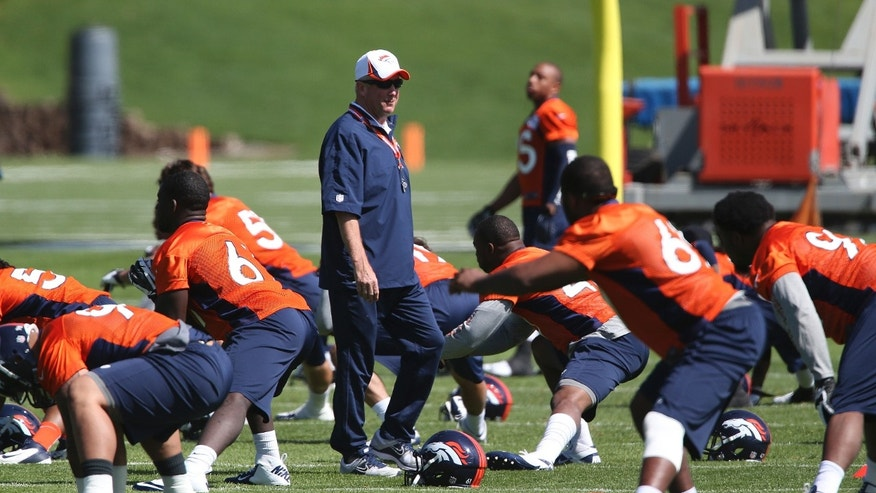Denver Broncos head coach John Fox, center, watches as defensive players stretch during off season training camp at the NFL football team's training facility in Englewood, Colo., on Monday, May 10, 2013. (AP Photo/Ed Andrieski)