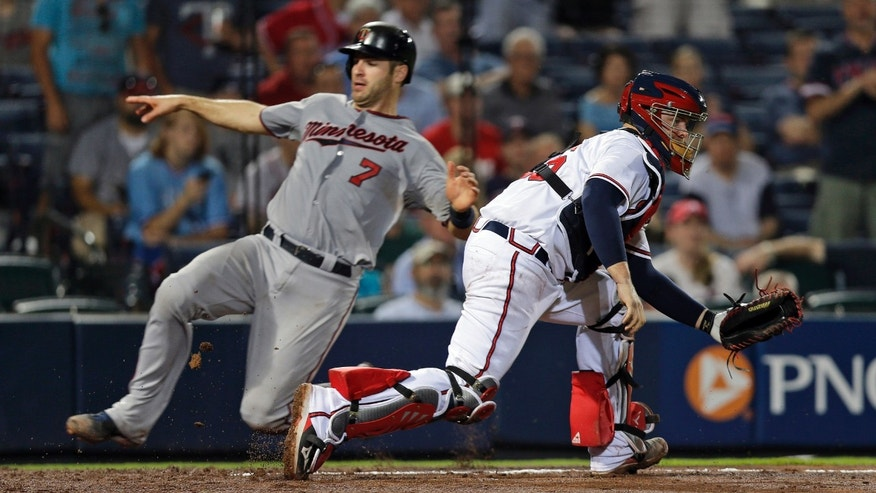 Minnesota Twins' Joe Mauer (7) scores as Atlanta Braves catcher Brian McCann (16) handles the late throw in the eighth inning of a baseball game, Tuesday, May 21, 2013 in  in Atlanta. (AP Photo/John Bazemore)