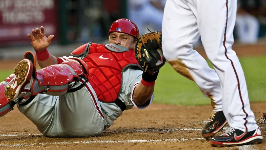 Philadelphia Phillies' Carlos Ruiz, left, dives in vain to tag Arizona Diamondbacks'Paul Goldschmidt on Friday, May 10, 2013, in Phoenix.