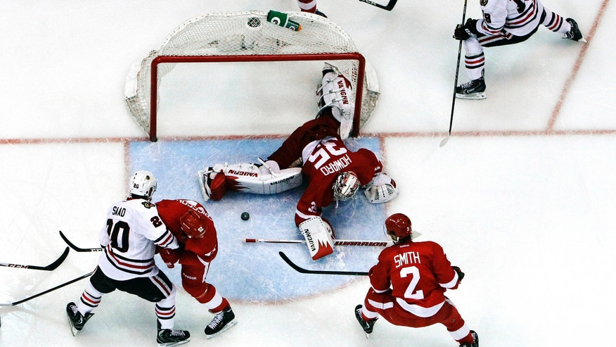 Detroit Red Wings goalie Jimmy Howard (35) stops a shot by Chicago Blackhawks center Jonathan Toews (19) during the second period of an NHL hockey Stanley Cup playoffs Western Conference semifinal game in Detroit, Monday, May 20, 2013. Detroit won 3-2. (AP Photo/Paul Sancya)
