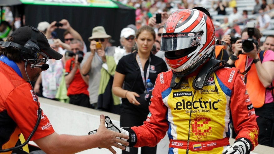 "Carlos Munoz, of Colombia, is congratulated by a crew member after a qualification run on the first day of qualifications for the Indianapolis 500 auto race at Indianapolis Motor Speedway in Indianapolis, Saturday, May 18, 2013. Munoz later qualified in second place with a speed of of 228.342 mph. in the ""Fast Nine"" session. (AP Photo/Darron Cummings)"