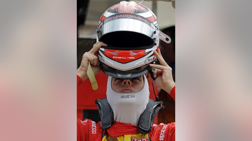 Carlos Munoz, of Colombia, puts on his helmet as he prepares to drive during practice for the Indianapolis 500 auto race at the Indianapolis Motor Speedway in Indianapolis, Friday, May 17, 2013. (AP Photo/Darron Cummings)
