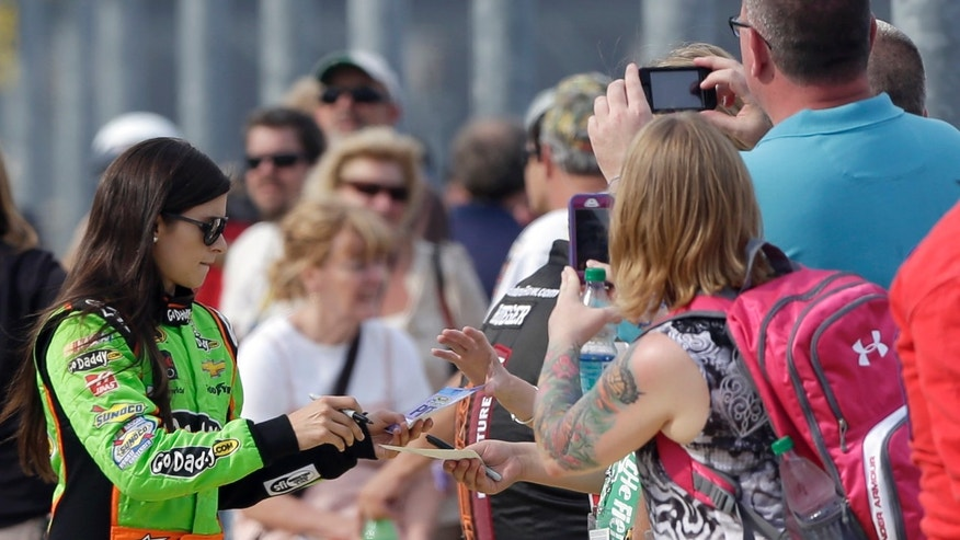 Danica Patrick, left, signs autographs before qualifying for the NASCAR Sprint Showdown auto race at Charlotte Motor Speedway in Concord, N.C., Friday, May 17, 2013. (AP Photo/Chuck Burton)