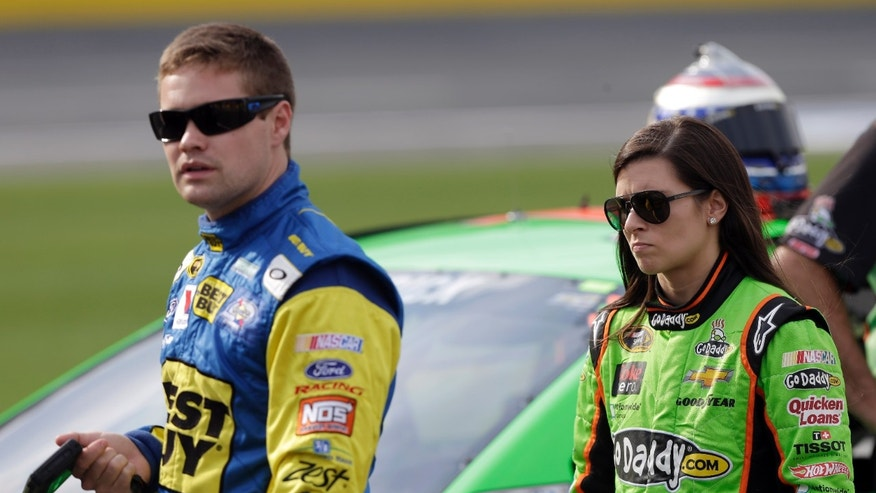 Danica Patrick, right, walks with boyfriend Ricky Stenhouse Jr., left, on pit road during qualifying for the NASCAR Sprint Showdown auto race at Charlotte Motor Speedway in Concord, N.C., Friday, May 17, 2013. (AP Photo/Chuck Burton)