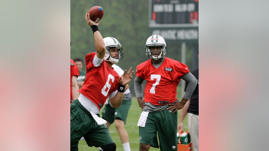 New York Jets' Mark Sanchez (6) throws a pass as Geno Smith (7) looks on as the quarterbacks practice during NFL football practice in Florham Park, N.J., Wednesday, May 22, 2013. (AP Photo/Mel Evans)