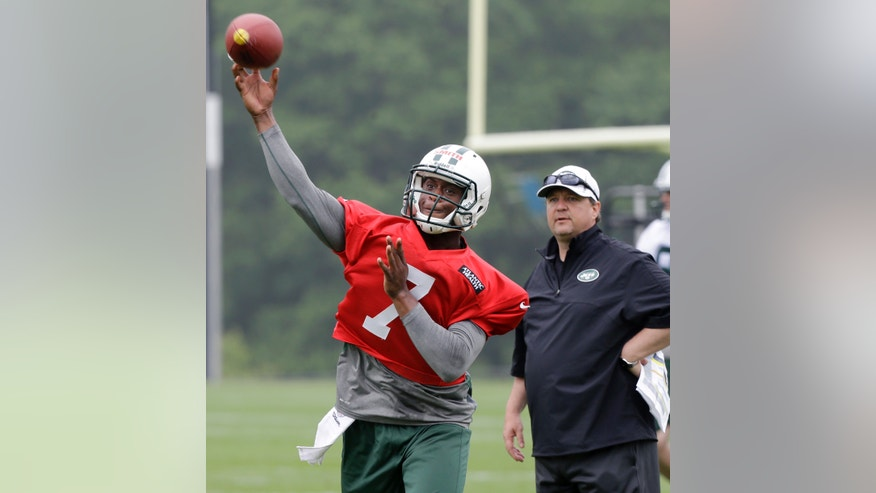 New York Jets offensive coordinator Marty Mornhinweg, right, looks on as quarterback Geno Smith (7) throws a pass during NFL football practice in Florham Park, N.J., Wednesday, May 22, 2013. (AP Photo/Mel Evans)