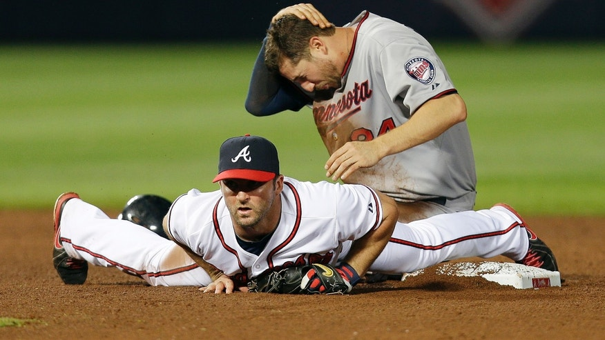 Minnesota Twiins' Trevor Plouffe (24) holds his head after he was injured on a force play at second base with Atlanta Braves second baseman Dan Uggla (26) on a ground ball in the ninth inning of a baseball game Tuesday, May 21, 2013 in  in Atlanta. (AP Photo/John Bazemore)