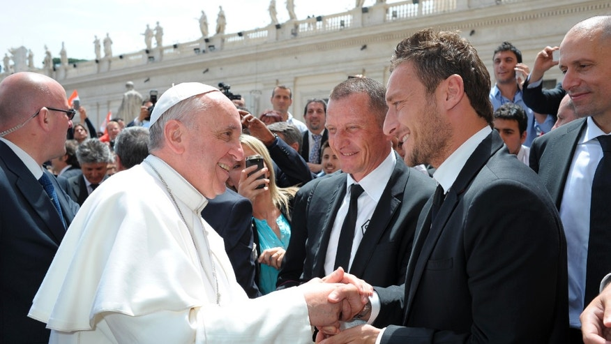 In this photo provided by the Vatican newspaper L'Osservatore Romano, Pope Francis meets AS Roma's Francesco Totti, right, as AS Roma coach Aurelio Andreazzoli looks on, at the end of his weekly general audience at St. Peter Square at the Vatican Wednesday, May 22, 2013. (AP Photo/L'Osservatore Romano, ho)