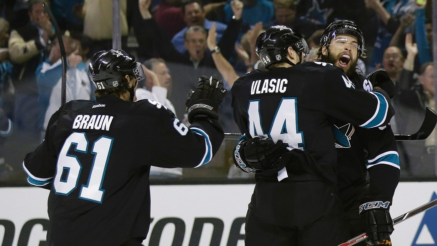 San Jose Sharks' Brent Burns, right, celebrates his goal with teammates Marc-Edouard Vlasic (44) and Justin Braun (61)  against the Los Angeles Kings during the first period in Game 4 of their second-round NHL hockey Stanley Cup playoff series in San Jose, Calif., Tuesday, May 21, 2013. (AP Photo/Marcio Jose Sanchez)