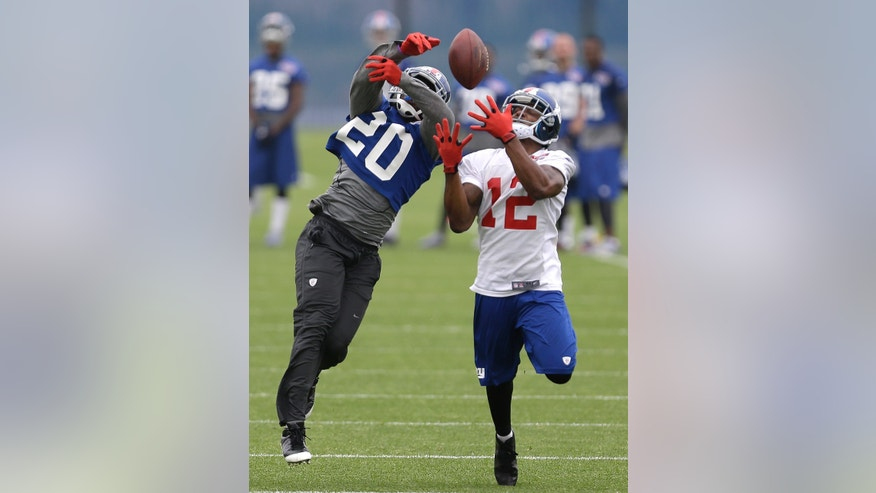 New York Giants' Prince Amukamara, left, defends against Jerrel Jernigan on a pass from Eli Manning during NFL football camp, Wednesday, May 22, 2013, in East Rutherford. (AP Photo/Julio Cortez)