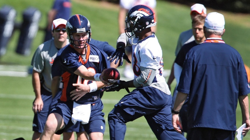 Denver Broncos quarterback Peyton Manning hands the ball off to wide receiver Demaryius Thomas during off season training camp at the NFL football team's training facility in Englewood, Colo., on Monday, May 10, 2013. Head coach John Fox watches at right. (AP Photo/Ed Andrieski)