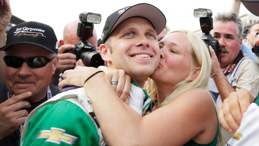 Ed Carpenter gets a kiss from his wife, Heather, after he won the pole for the Indianapolis 500 auto race on the first day of qualifications at Indianapolis Motor Speedway in Indianapolis, Saturday, May 18, 2013. Carpenter won the pole with a speed of 228.762 miles per hour. (AP Photo/AJ Mast)