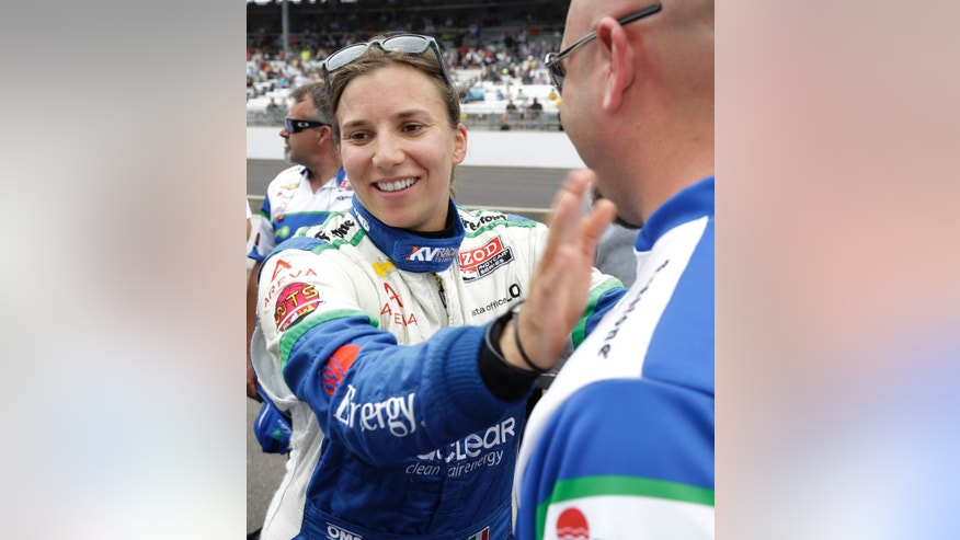 In this photo taken on Saturday, May 18, 2013, Simona de Silvestro, of Switzerland, reacts with a crew member after first day of qualifications for the Indianapolis 500 auto race at the Indianapolis Motor Speedway in Indianapolis. de Silvestro will be one of four women starting Sunday's race.(AP Photo/Tom Strattman)