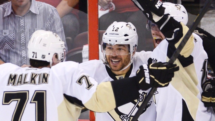 Pittsburgh Penguins' Jarome Iginla (12) is congratulated by teammates Evgeni Malkin (71) and James Neal after scoring against the Ottawa Senators during second-period NHL hockey playoff game action in Ottawa, Ontario, Wednesday, May 22, 2013. (AP Photo/The Canadian Press, Adrian Wyld)