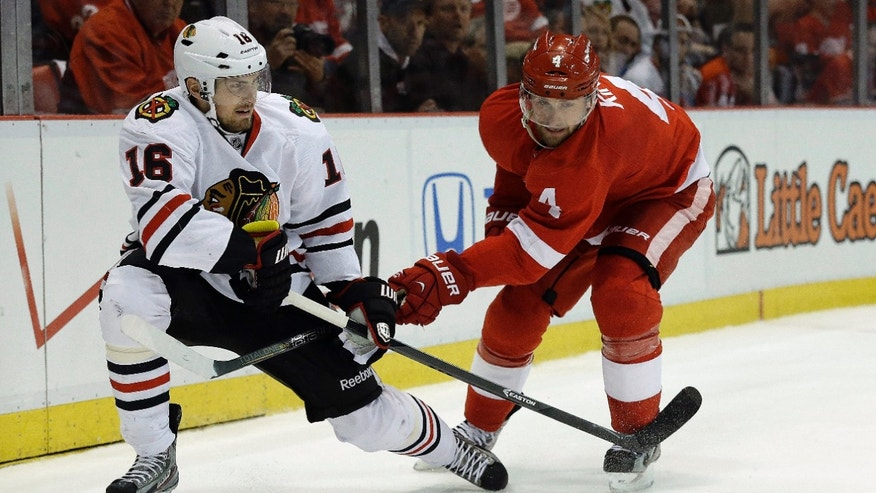 Detroit Red Wings defenseman Jakub Kindl (4), of the Czech Republic, defends against Chicago Blackhawks center Marcus Kruger (16), of Sweden, during the first period in Game 4 of the Western Conference semifinals in the NHL hockey Stanley Cup playoffs in Detroit, Thursday, May 23, 2013. (AP Photo/Paul Sancya)