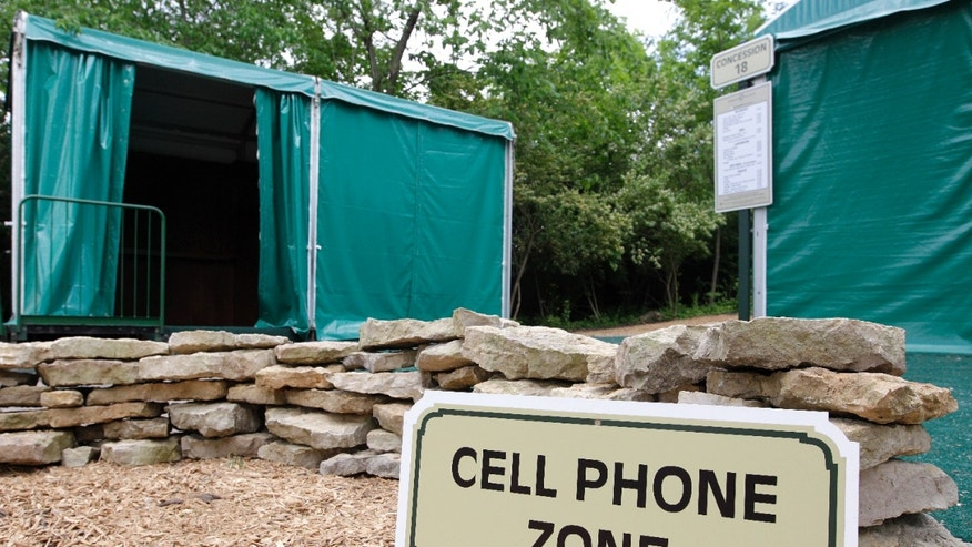 In this photo taken Wednesday, May 22, 2013, a cell phone zone located near a digital hub, left, and concession stand are shown at Muirfield Village Golf Club in Dublin, Ohio. The cell phone zones were created to keep fans' cell phone away from the course and the golfers, while the digital hubs will feature Memorial Tournament social media content and player information to allow fans to have a better experience. (AP Photo/Jay LaPrete)