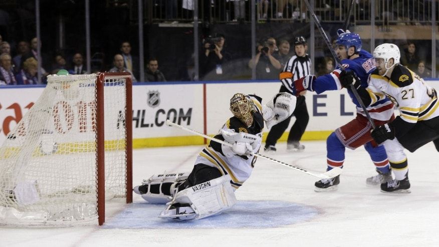 New York Rangers' Chris Kreider, center, reacts as the winning-goal goes past Boston Bruins goalie Tuukka Rask, left, while Dougie Hamilton looks on during the overtime period in Game 4 of the Eastern Conference semifinals in the NHL hockey Stanley Cup playoffs, Thursday, May 23, 2013, in New York. The Rangers won 4-3. (AP Photo/Seth Wenig)