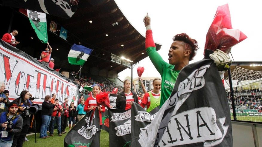 FILE - In this April 21, 2013, file photo, Portland Thorns goalie Karina LeBlanc, right, celebrates with teammates and fans after their 2-0 win over the Seattle Reign in a National Women's Soccer League match in Portland, Ore. The Thorns' season couldn't be going any better. They're sitting atop the league standings and drawing more than 10,000 fans to home games. AP Photo/Don Ryan, File)