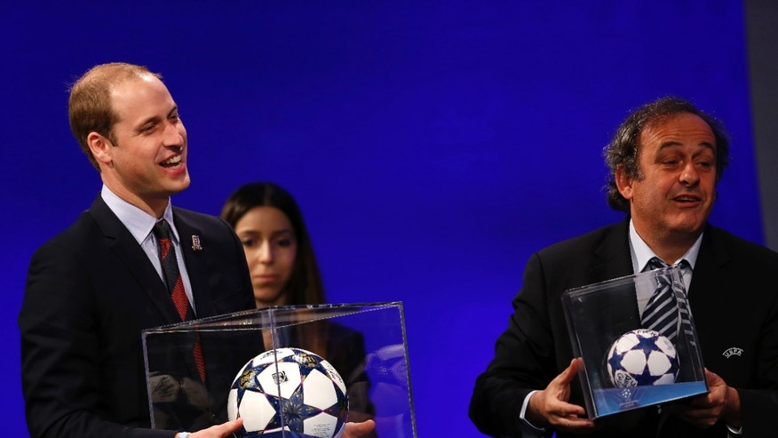 President of English Football Association Prince William, left, holding a football presented to him, reacts as UEFA President Michel Platini presents him with a mini soccer ball also after he addressed the delegates during the 37th Ordinary UEFA Congress in London, Friday, May 24, 2013. (AP Photo/Sang Tan)